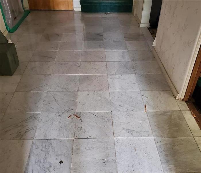 This is a before picture of a tile hallway floor.